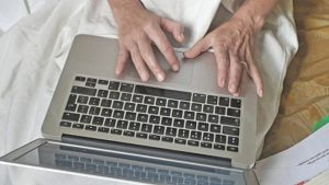 Close up photo of a laptop on someone's lap with their hands touching the keyboard