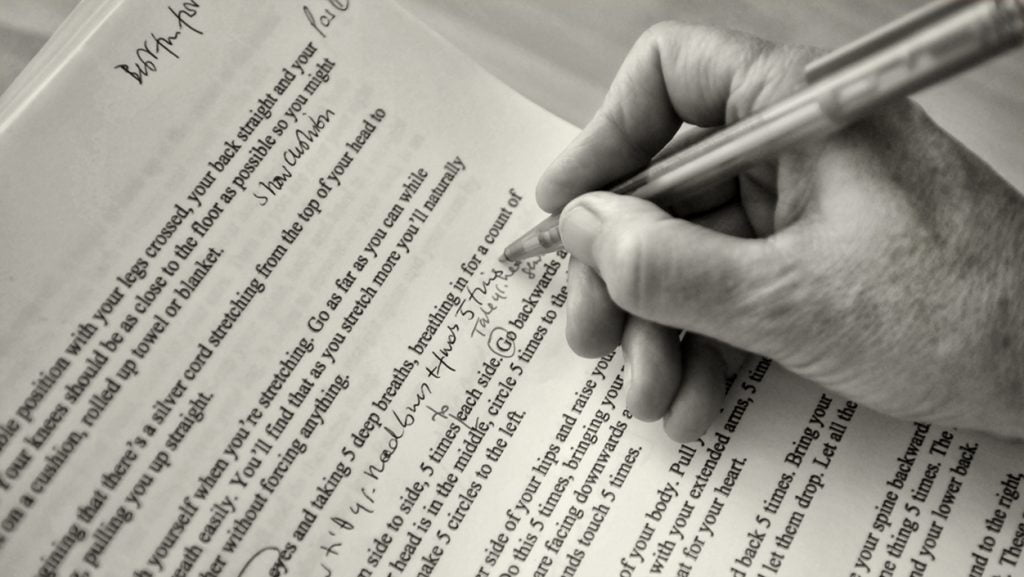 A close up of a hand holding a pen, writing notes on printed text.