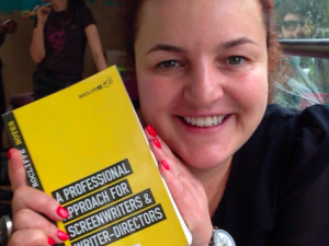 Photo of BAFTA Rocliffe founder Farah Abushwesha holding her book 'A Professional Approach for Screenwriters and Directors'.